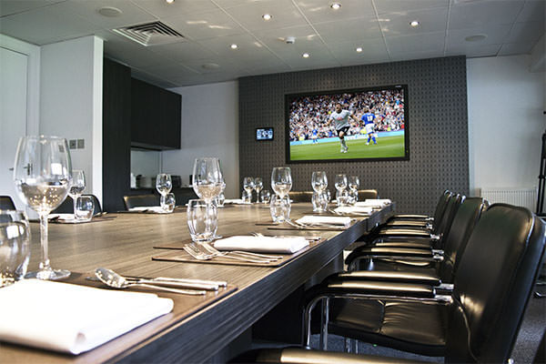 "The Cinos Suite, laid out for match day dining, showing the 80"" NEC screen and AMX touch panel ready for ordering directly from the bar."