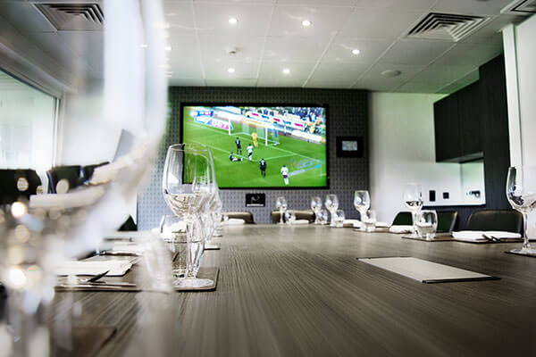 "The Cinos Suite, showing the 80"" NEC screen and AMX wall mounted panel."